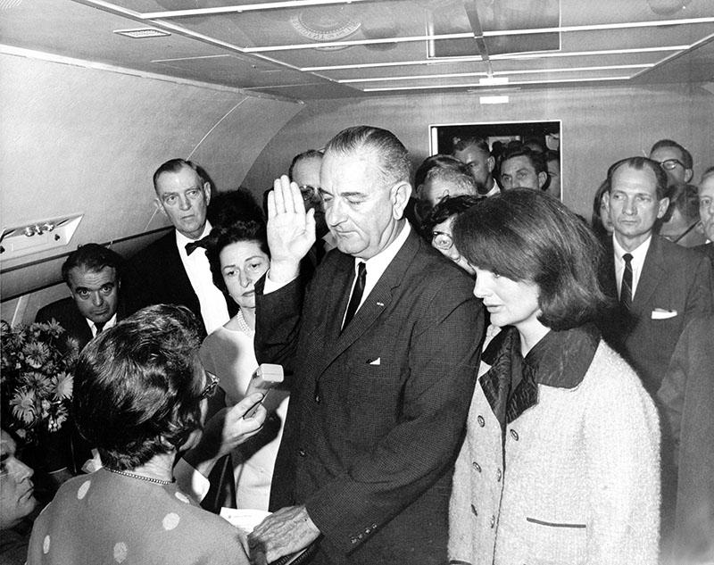Johnson leteszi az elnöki esküt, balján Jackie Kennedy férje vérétől áztatott ruhájában