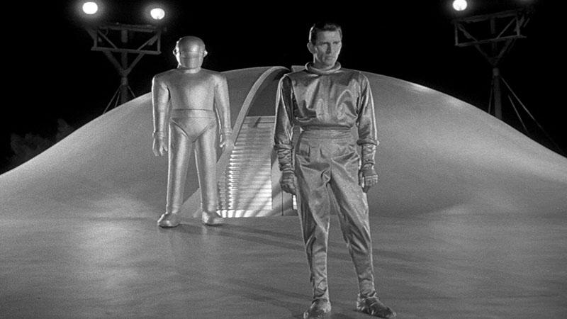 A Michael Rennie által alakított Klaatu, háttérben a védelmező robot, Gort