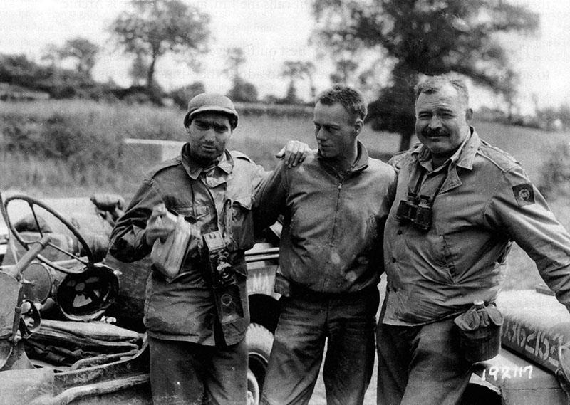 Bajtársak közt, bal szélen Robert Capa, jobb oldalt Ernest Hemingway